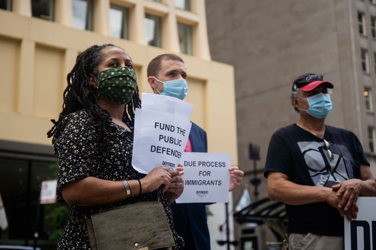 Fasika Alem, programs director of the United African Organization, holds a sign during a press conference outside the Richard J. Daley Center Wednesday morning, July 22, 2020.