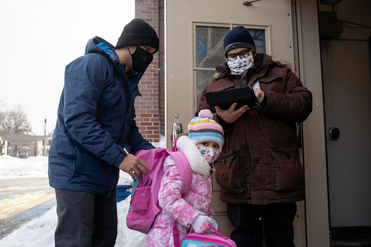 Amilcar Marquez drops off his daughter, Isabella, at Disney II Magnet Elementary School in the Old Irving Park neighborhood on Thursday, Feb. 11, 2021.