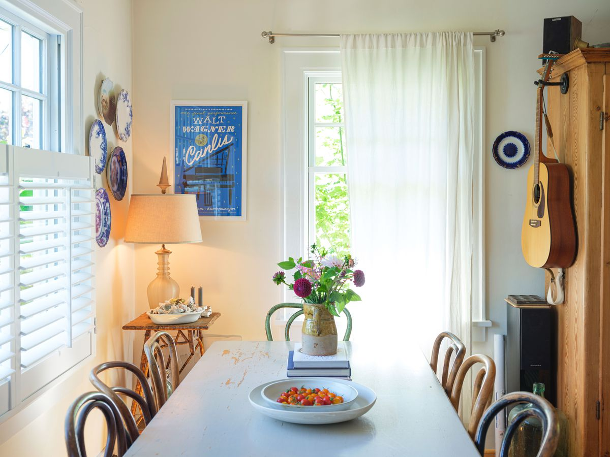 A dining area with a table, chairs, and a wooden cabinet. Hanging on the walls are a guitar, plates, and a poster. There is a vase with flowers and a bowl with tomatoes on the table.