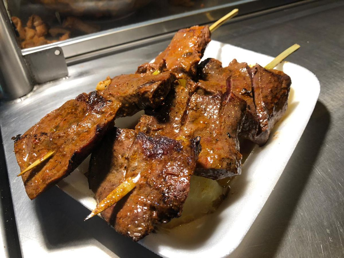 Two skewers with large hunks of grilled beef glisten on a white paper plate resting on a steel counter