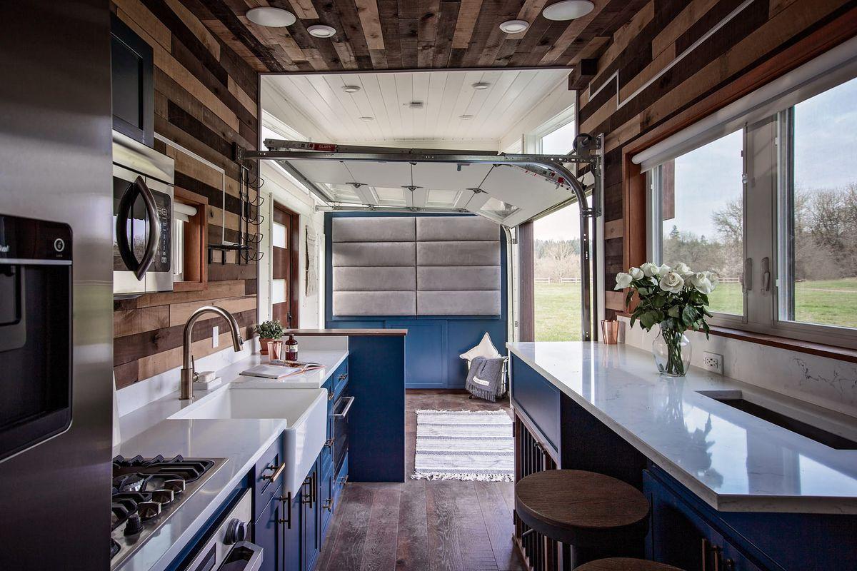Tiny home kitchen looking onto living room with open door