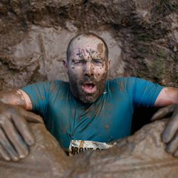 TELFORD, ENGLAND - JANUARY 27: A competitor emerges from an underground tunnel during the Tough Guy Challenge on January 27, 2013 in Telford, England.