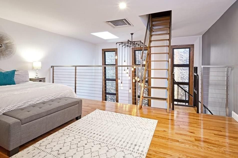 A bedroom loft next to a railing and there's a steep staircase leading up from the loft.