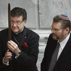"""Rev. Ray Waldon of the Cathedral Church of Saint Mark, left, and Alan Bachman of Chabad Lubavitch pass a peace pipe during a """"blessing ceremony"""" to mark the first day of Interfaith Month at the Utah State Capitol in Salt Lake City on Friday, Feb. 1, 2013."""