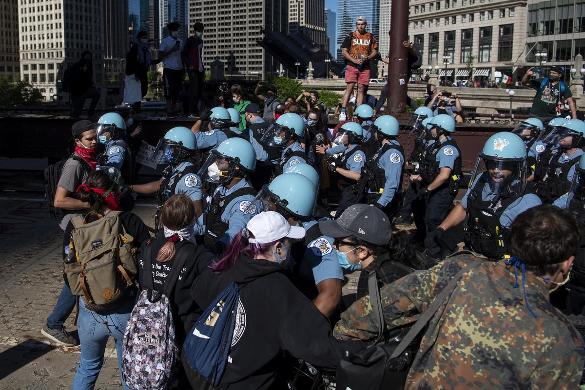 Chicago police push through a line of protesters to take Wabash Bridge, Saturday, May 30, 2020.