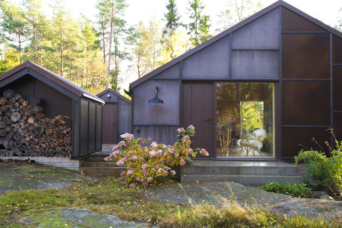 Three metal-framed homes in the woods.