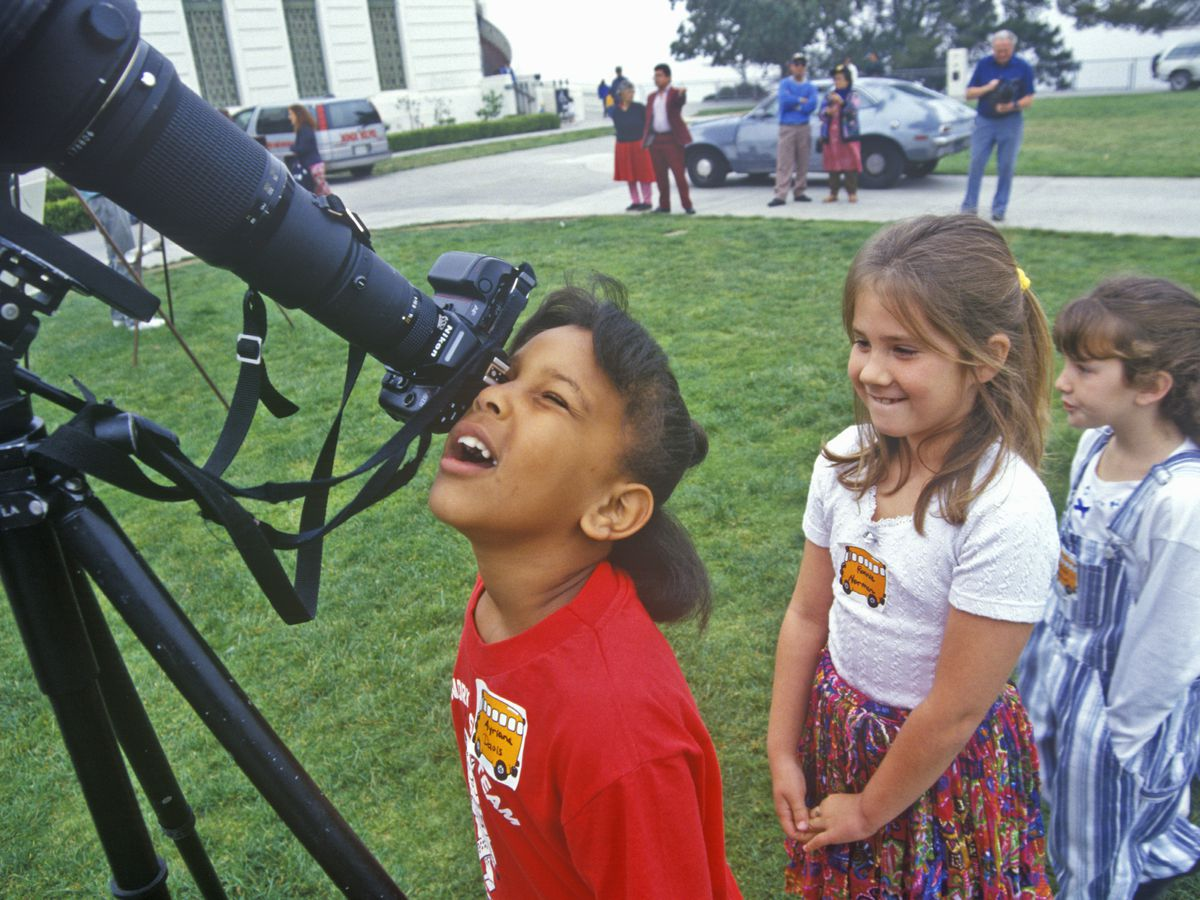 Children line up behind a telescope. There is a child looking through one eye through the lens of the telescope.