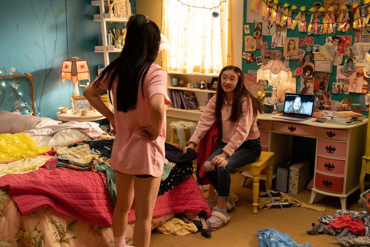 A messy teen bedroom with teal walls, clothes and books everywhere, a bed with a magenta quilt, and a wall covered in a collage of drawings and photographs. One girl is standing with her arms on her hips and another girl is sitting in a chair at a vanity table.