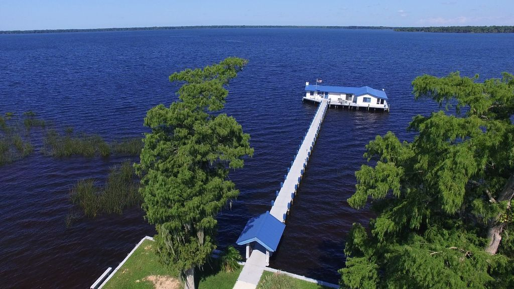 An aerial view of Crescent Lake in Florida. There is a dock spanning out over the lake. At the edge of the dock is a white house with a blue roof. There are trees on the edge of the waterfront.