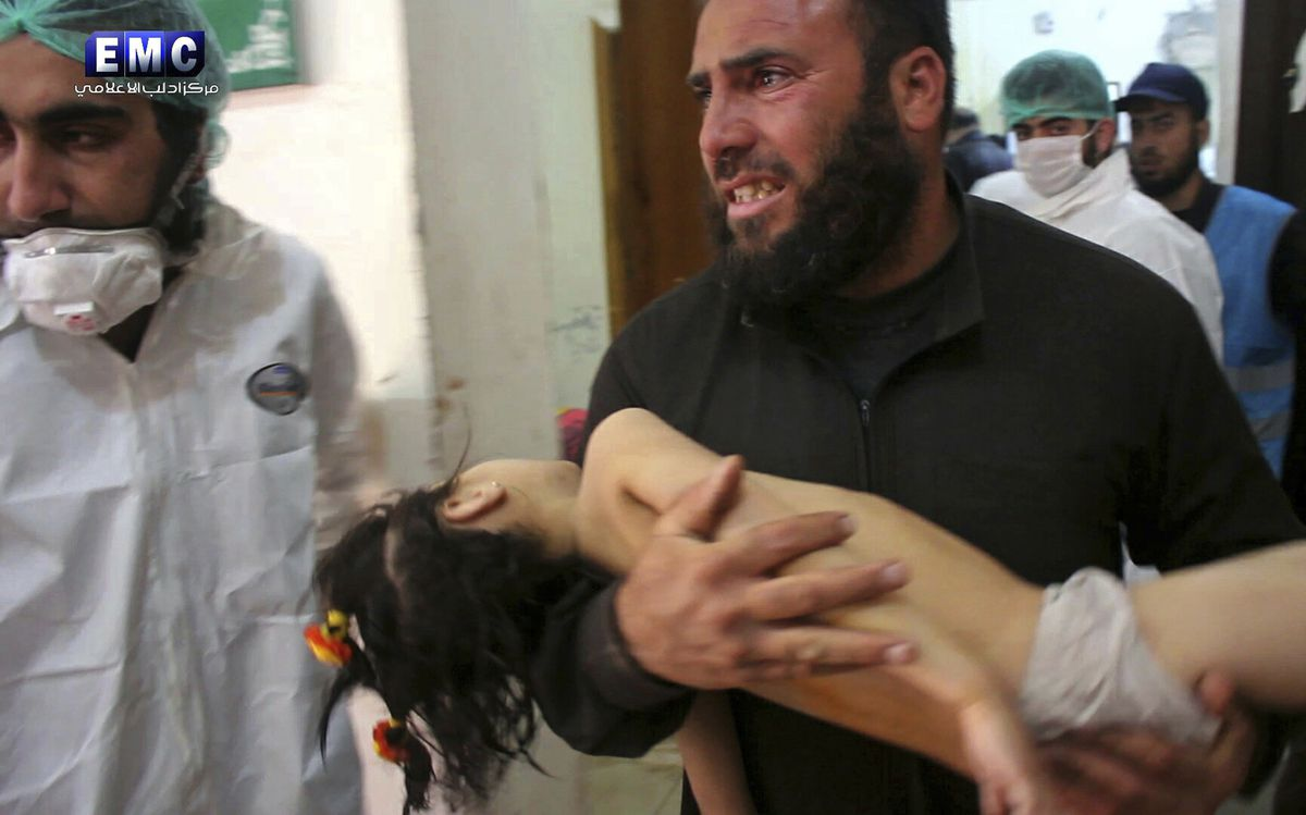 This photo provided by the Syrian anti-government activist group Edlib Media Center, shows a man carrying a child following a suspected chemical attack, at a makeshift hospital in the town of Khan Sheikhoun, northern Idlib province, Syria. The suspected c