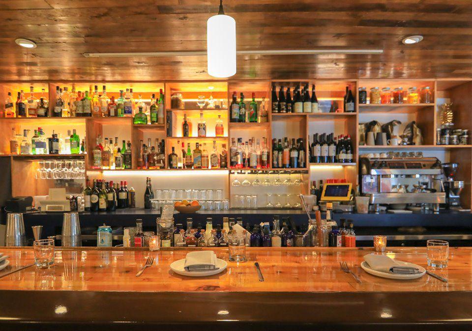 A wooden bar with many many alcohols