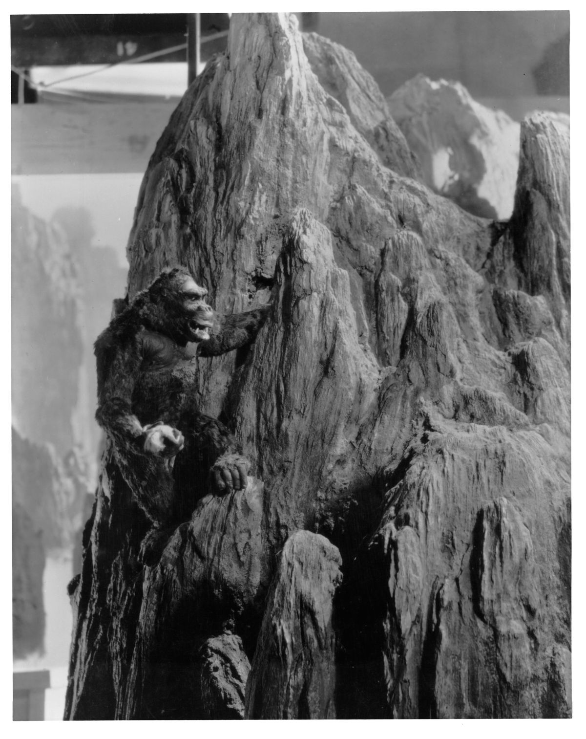 A black and white still image of a gorilla miniature climbing a psuedo rocky mountain.