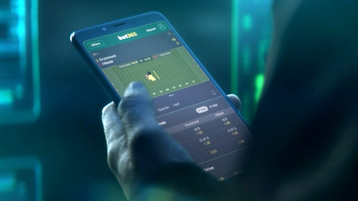 """Photo of a hand holding a smart phone - Screen reads """"Bet365"""" and has a computer graphic image  of a football player."""