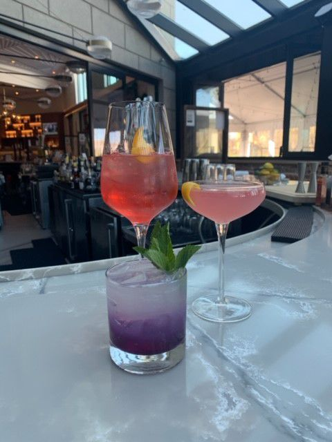 Two pink cocktails and one purple cocktail on a white bartop