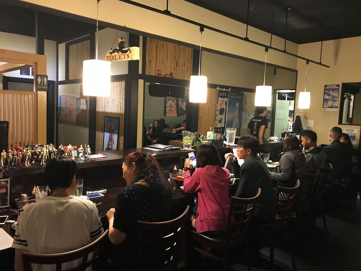 Insider of restaurant with people seated at the bar.