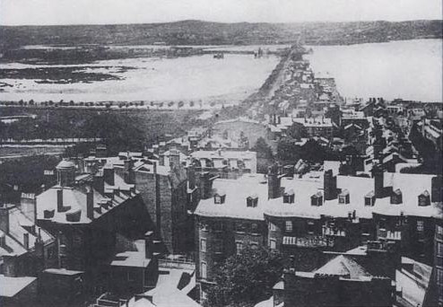 A historic photo in black and white of the Back Bay area of Boston. There are various city buildings. In the distance is a river.