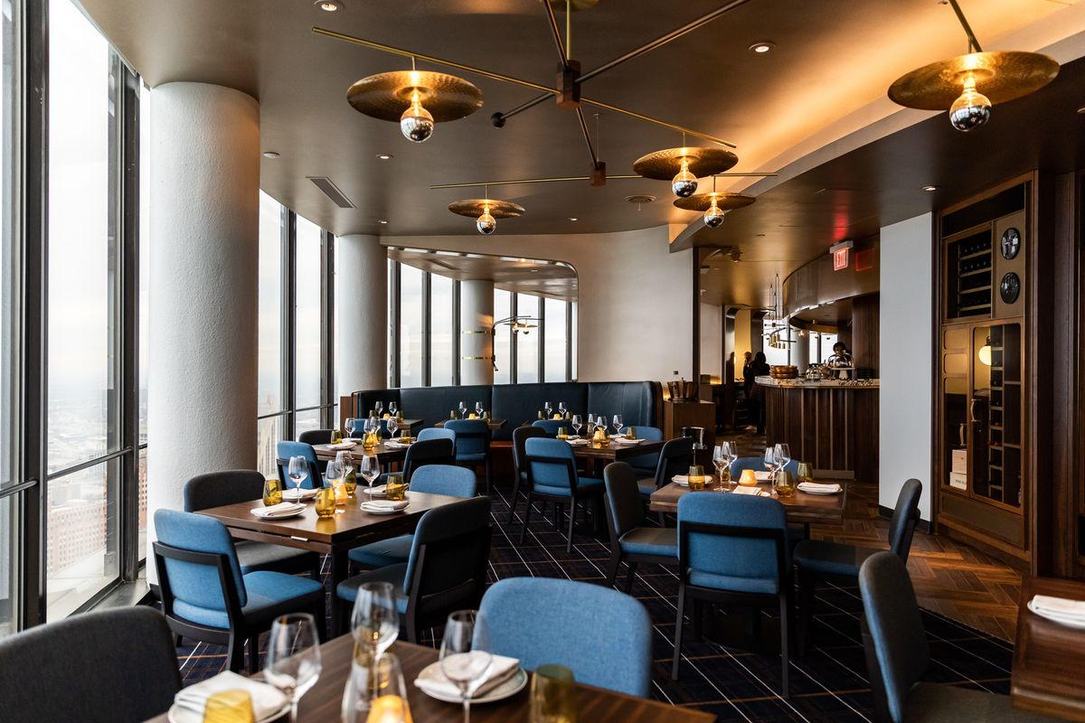 Brass light fixtures hang over tables with blue backed chairs.