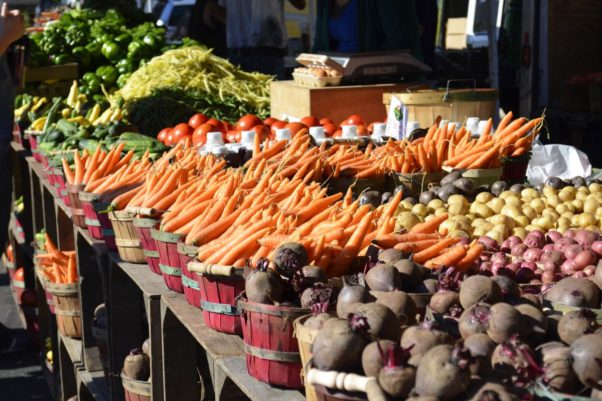 Dark red baskets containing carrots, beats, potatoes, long beans, and greens on a long table at an outdoor farmers market