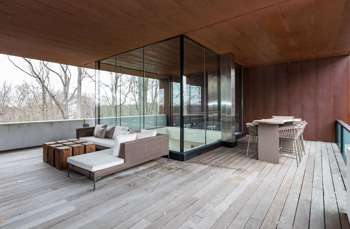 A covered outdoor patio features lounge couches, a dining table, and a glass cube that looks down into the living room below.