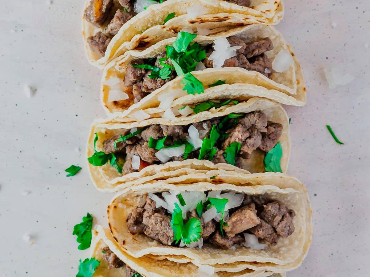 A lineup of flour tortillas stuffed with chopped steak, onions, and cilantro