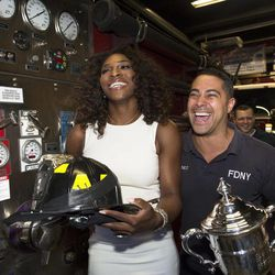 2012 U.S. Open Women's Singles champion Serena Williams laughs with fireman Freddy Martinez during a visit to the Engine 54 Ladder 4 Battalion 9 firehouse in midtown, Monday, Sept. 10, 2012, in New York. This year alone, Williams claimed the U.S. Open trophy alongside the gold medals she won at the London Olympics and the silver plate she took home from Wimbledon.