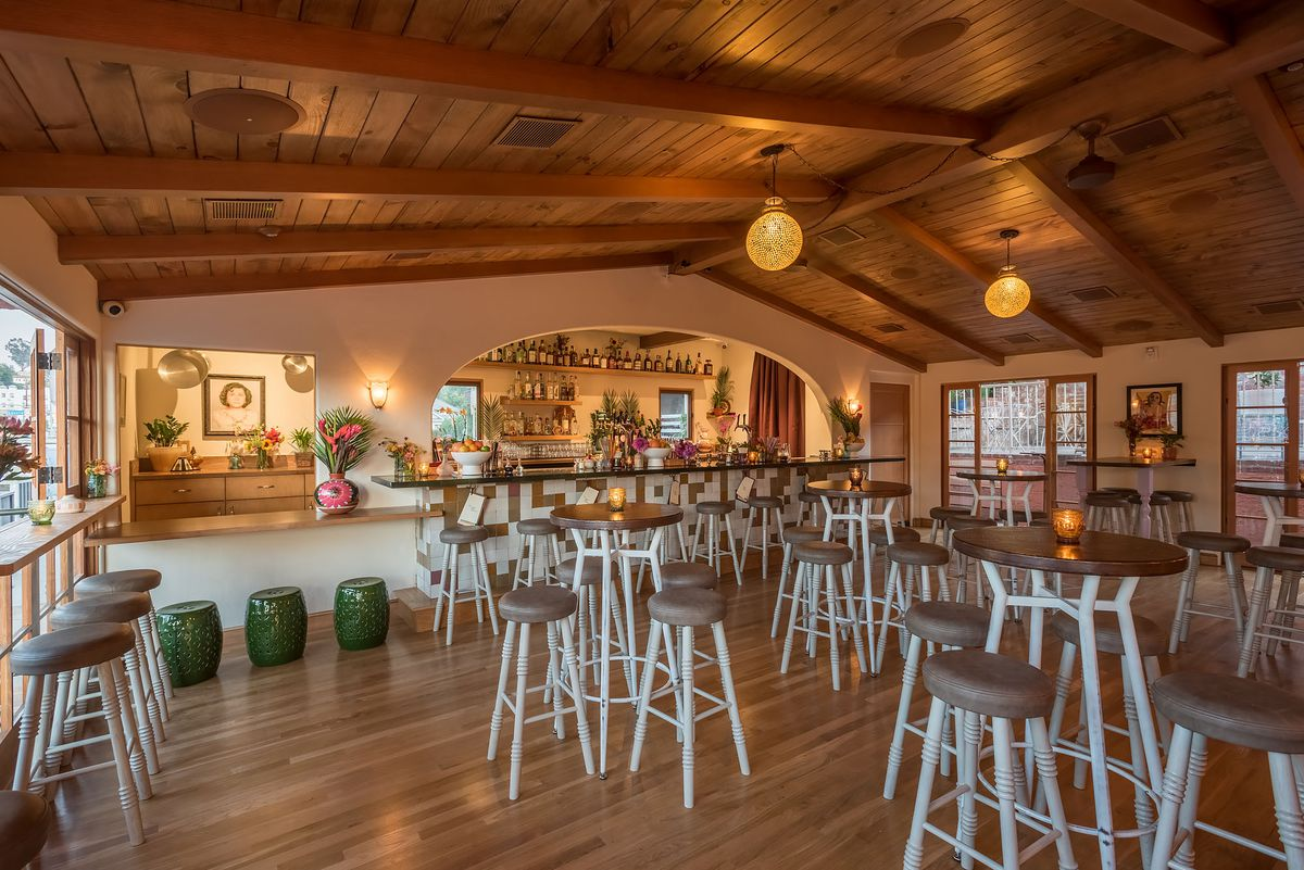 Interior of Bar Flores with low ceilings, white stools and bar tables.
