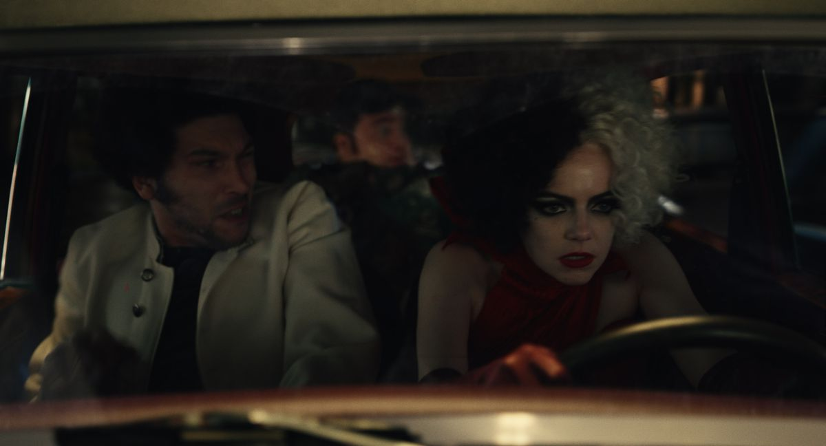Cruella drives a car poorly with Horace and Jasper looking on.