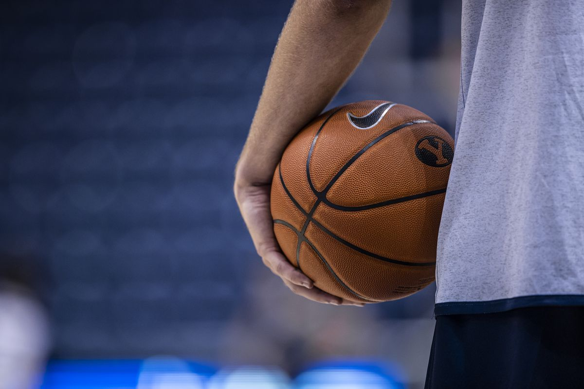 A BYU basketball player holds a ball during the first practice of the 2021 basketball season in the Marriott Center in Provo.