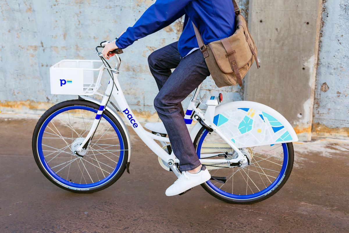 White and blue bicycle with person riding it photographed from shoulders down