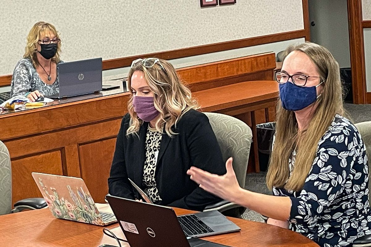 Michigan Teacher of the Year Leah Porter  addresses the state Board of Education during an October meeting. She is seated at the head of a conference table with Kacie Hook of Roscommon Middle School, who is the Teacher of the Year for Region 2. Both have open laptops in front of them.