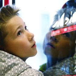 Hudson Ryan looks at the many different items inside a charity vending machine as he his brother Schroeder and their parents, Brittany and Travis Ryan, join other visitors to the Joseph Smith Memorial Building in Salt Lake City at Light the World vending machines on Friday, Dec. 15, 2017.