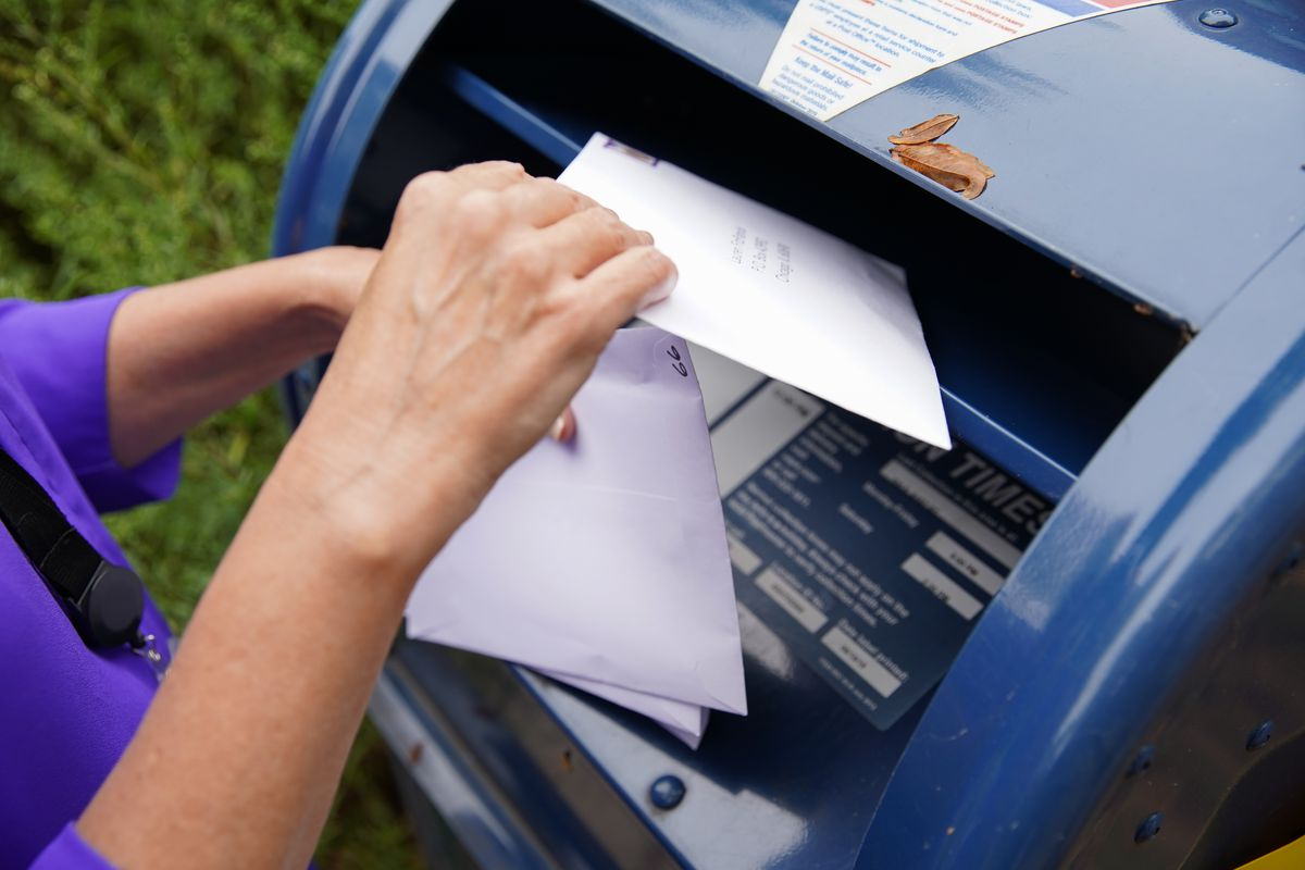 A woman mails an envelope in Hyde Park on Wednesday. As of Wednesday, 1.45 million Illinois voters applied to vote by mail — 50,000 of them since Tuesday.