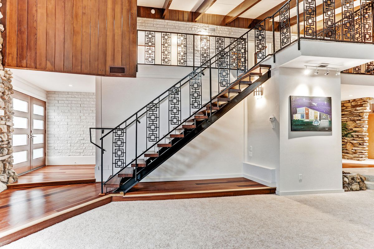 A view of a steel geometric staircase that goes upstairs to bedrooms.