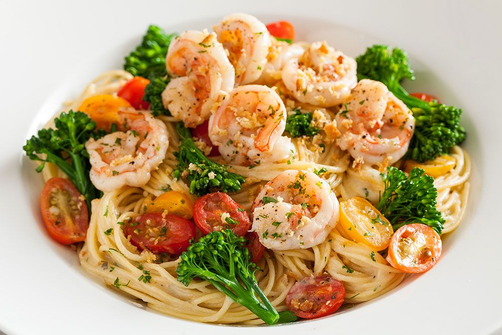 A bowl of garlic shrimp with pasta, tomatoes, and broccoli