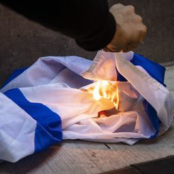 A small group of protesters try to burn the flag of Israel as thousands rally in support of Palestine and march through the Loop, Wednesday evening, May 12, 2021.