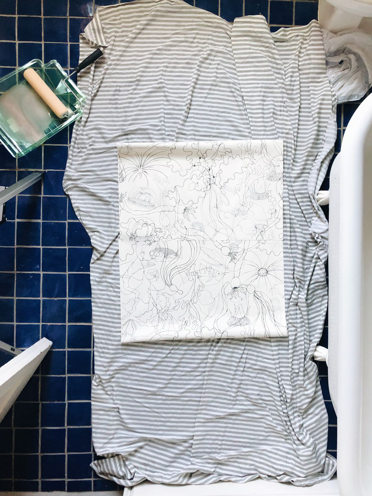 Minimalist wallpaper sits on top of a piece of fabric on the royal blue tile of the bathroom.
