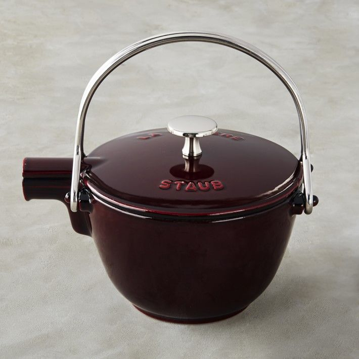 A dark red cast-iron tea kettle