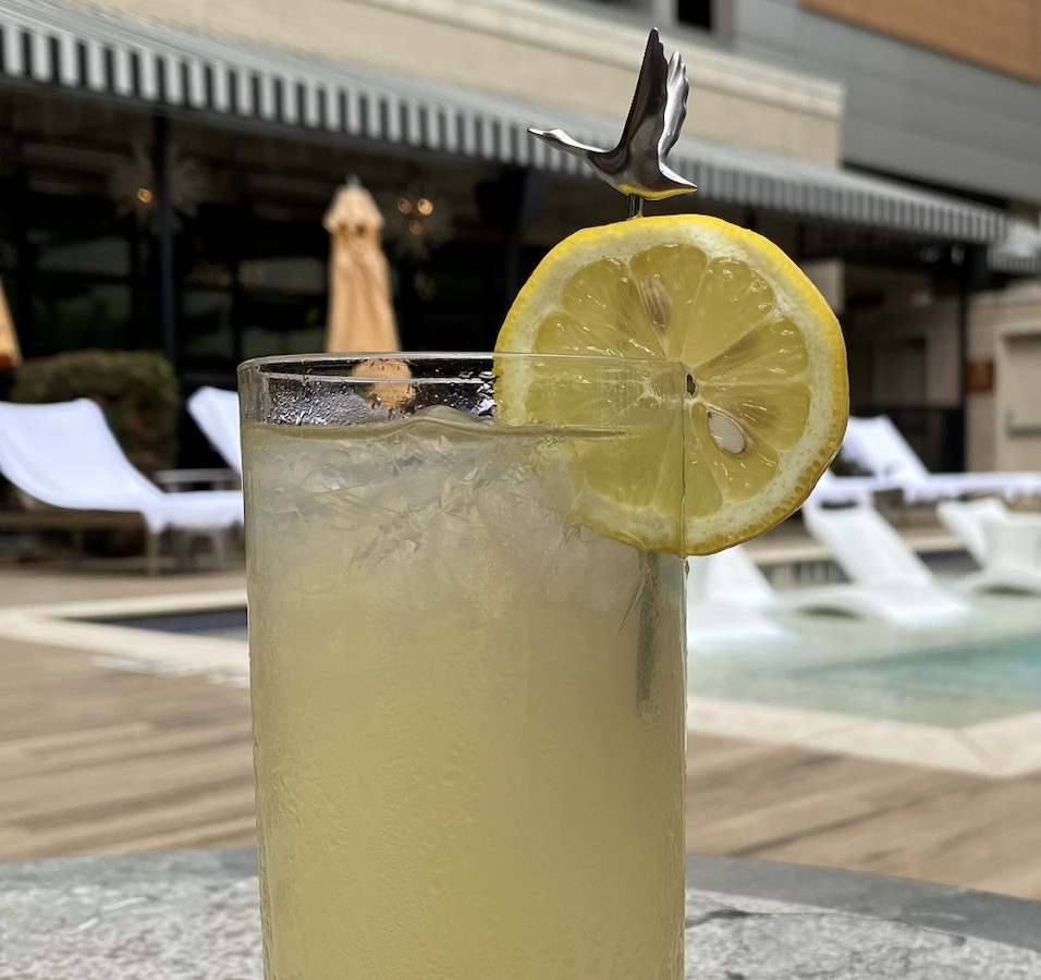 A yellow cocktail has a lemon slice on the rim.