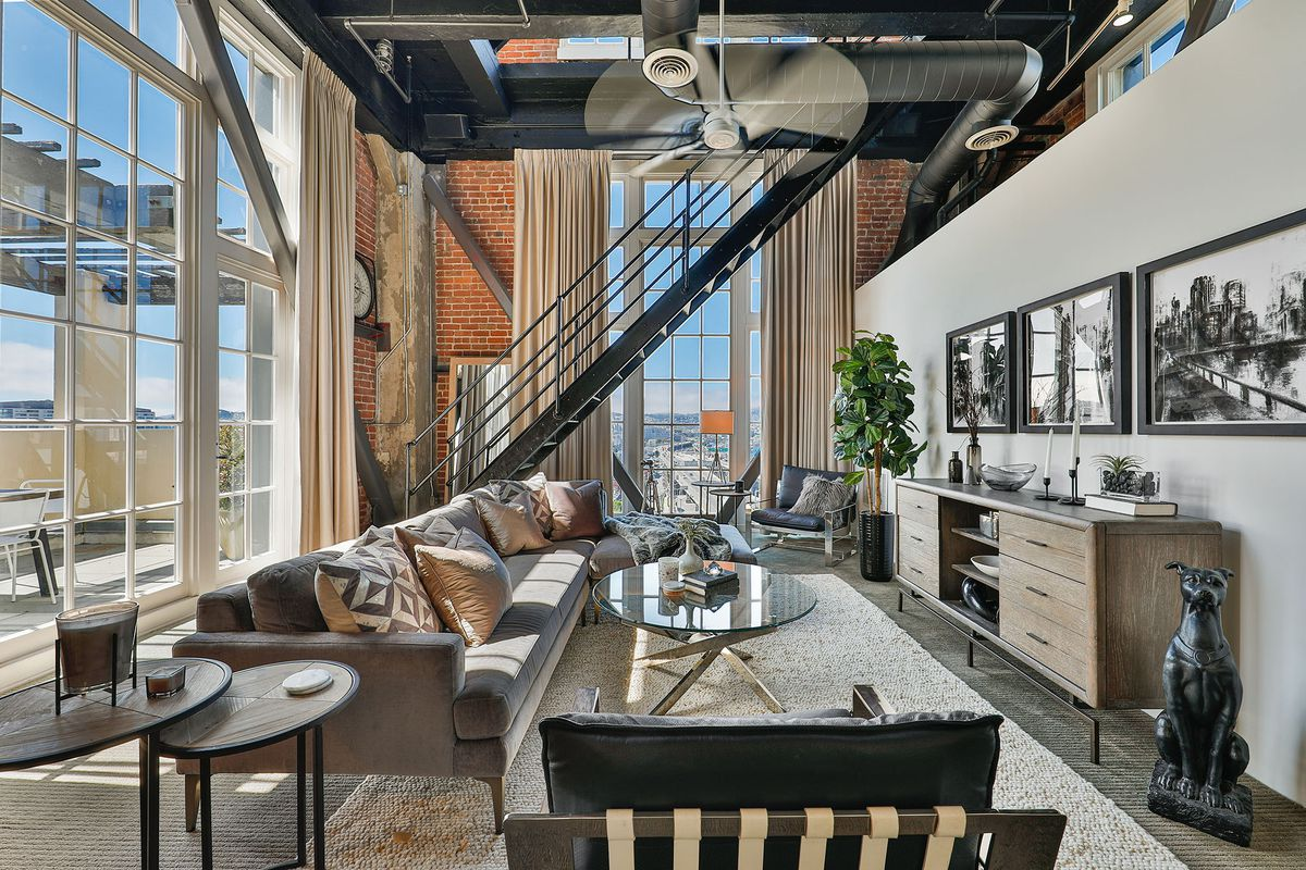 A brick room with a couch, glass coffee table, warehouse windows, and a metal staircase at the far end.