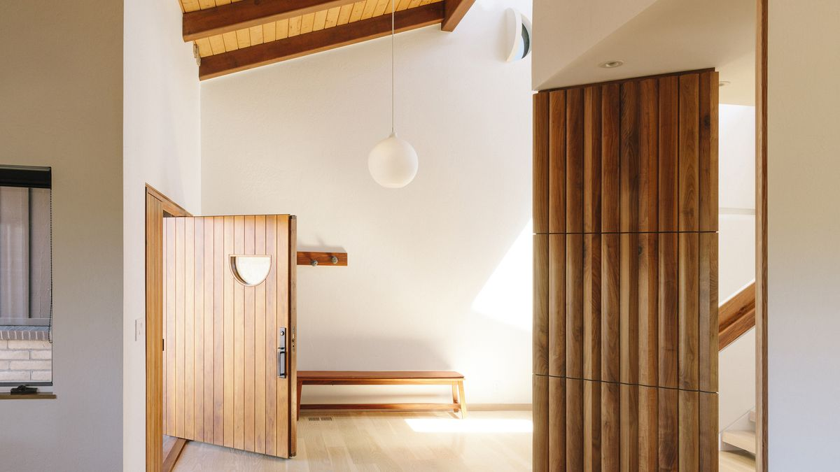 An entryway which is painted white. The door is made of wood. There is a wooden room partition on one side of the area. There is a hanging light fixture.
