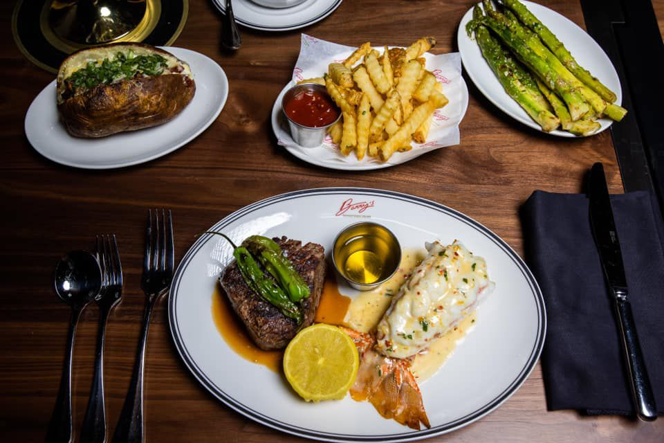 Steak and lobster, French fries, and asparagus