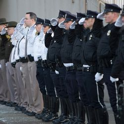 Law enforcement officers stand at attention as Unified police officer Doug Barney's casket arrives at the Maverik Center in West Valley City on Monday, Jan. 25, 2016.