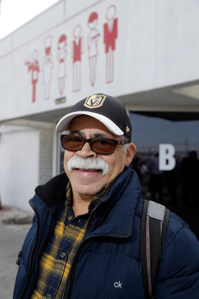 A man wearing sunglasses and a cap, with a neat mustache, poses outside the Culinary Union hall.