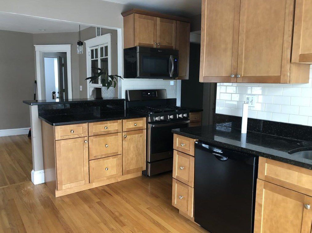 A kitchen with two counters meeting at a right angle.
