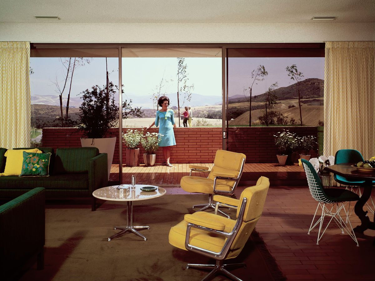 A living room furnished with a green sofa and yellow chairs. A woman on the outside patio looks through the glass doors.