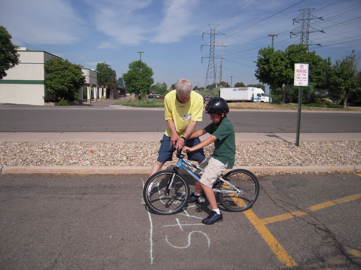 Jay Pierce, Bicycle and Pedestrian Safety Coordinator for the city of Aurora, goes over safety techniques with a bike rodeo participant.
