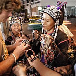 A tourist tries bargaining with a group of women at a street market in Bangkok.