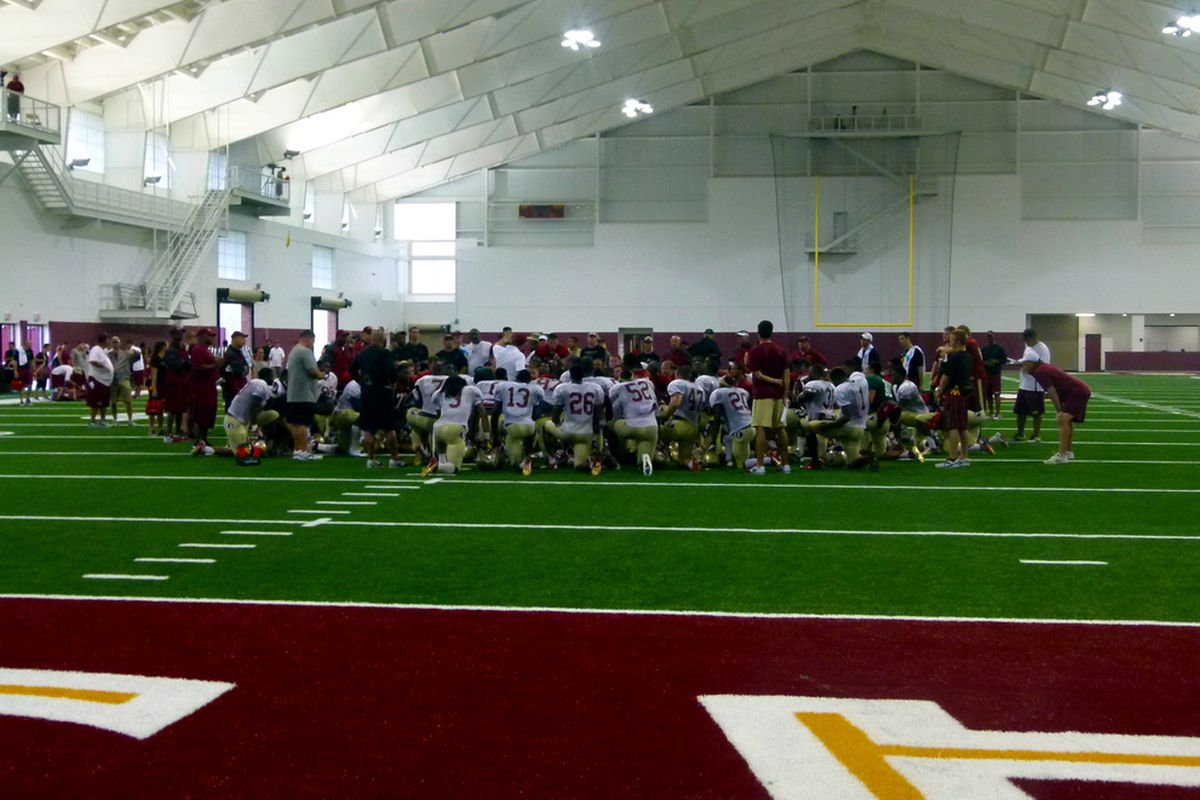 Team huddles after the open fall practice. Fans got to watch in the new Indoor Practice Facility.