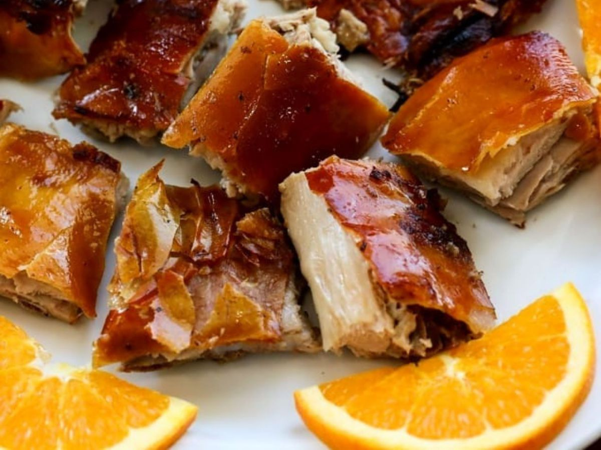 Chunks of roast pork with burnished skin and orange slices