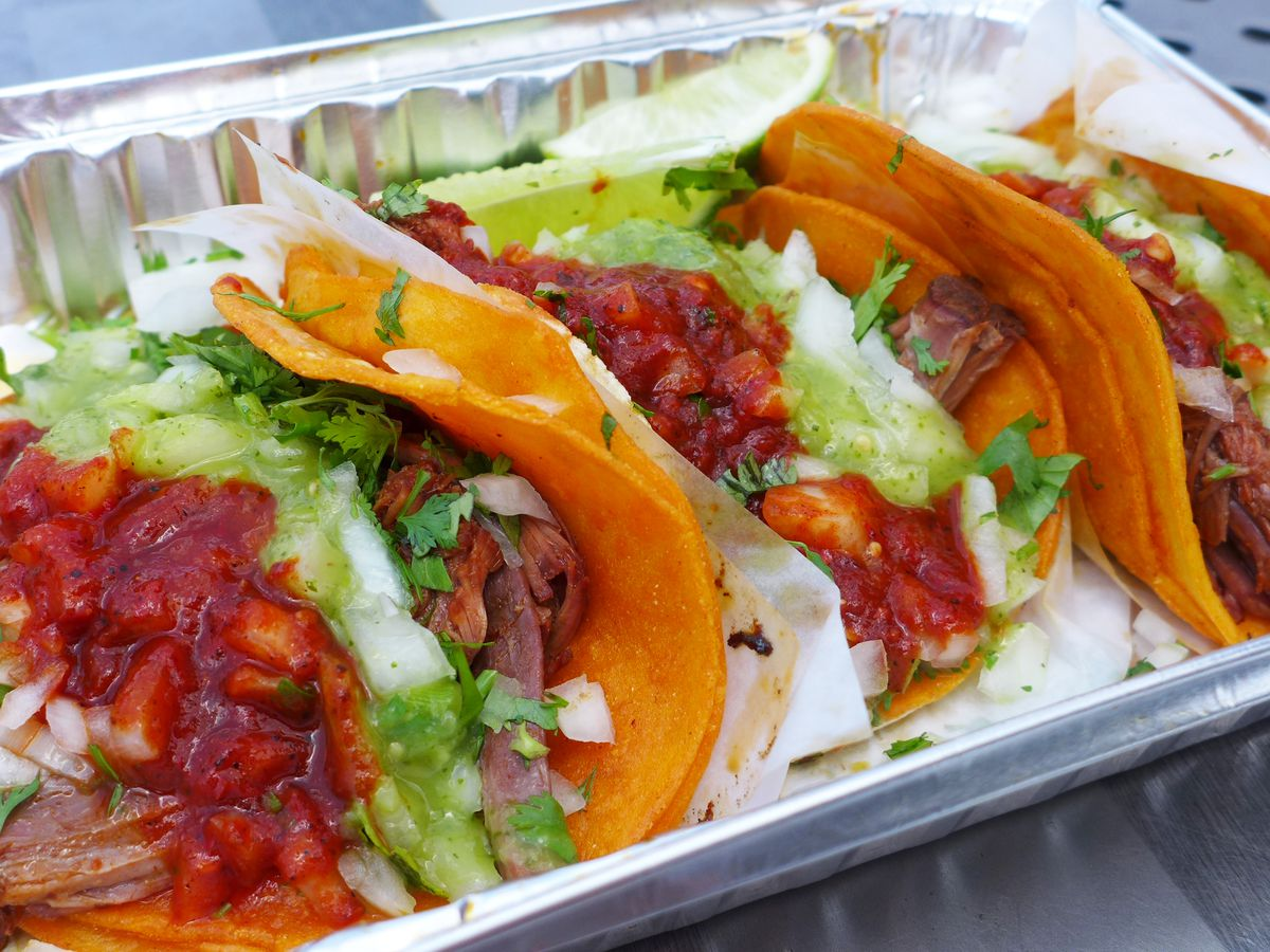 Three tacos with meaty red filling in an aluminum carryout container.